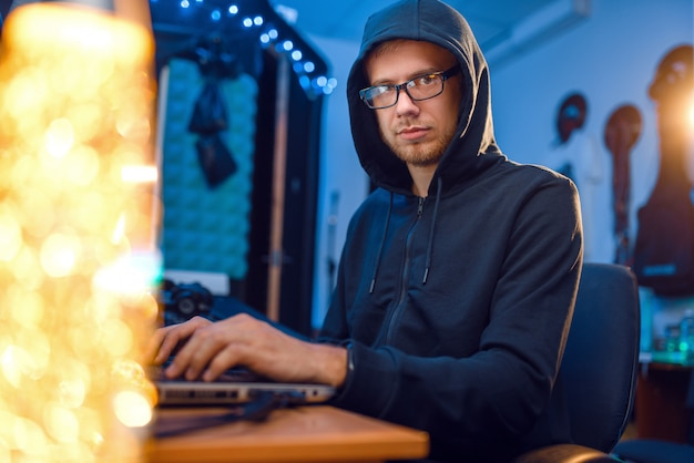 Hacker en campana en su lugar de trabajo con computadora portátil y de escritorio, piratería web o corporativa, usuario de darknet.