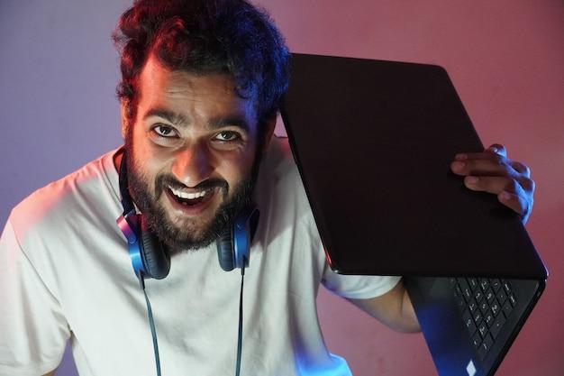 Un hacker chico con laptop y cara sonriente.