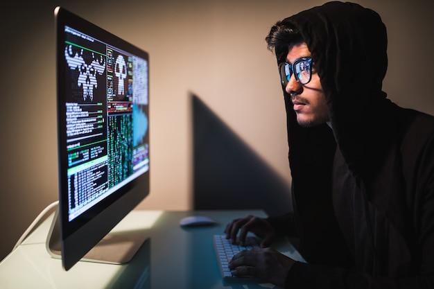 Hacker de indianmale con teléfono inteligente y codificación en la pantalla de la computadora en un cuarto oscuro