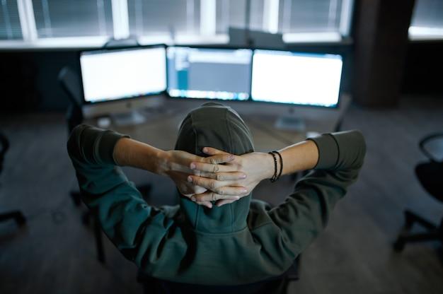 Hacker de internet masculino en el capó sentado en las pantallas, vista posterior. programador web ilegal en el lugar de trabajo, ocupación criminal. piratería de datos, seguridad cibernética