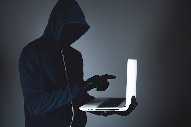 Hacker con laptop. crimen informático.