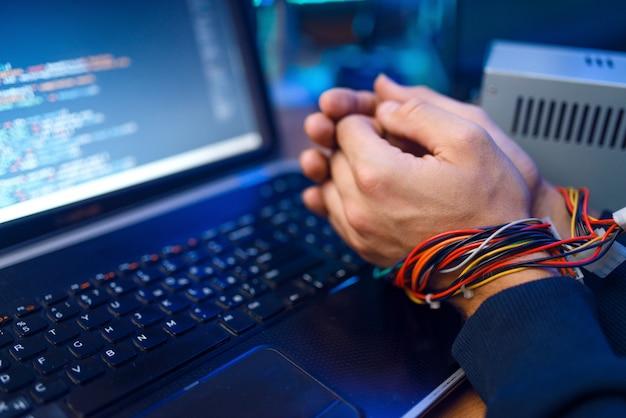 Hacker manos atadas con cables, darknet usando concepto, delito de información.