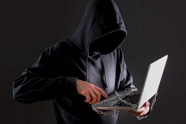 Hacker masculino con laptop protegida por cadena