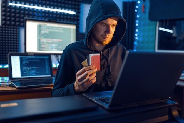 Hacker muestra tarjeta de crédito bancaria, piratería financiera