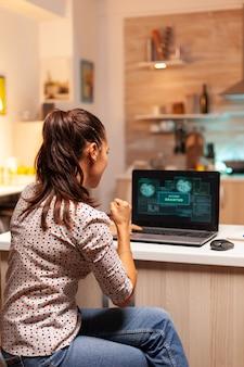 Hacker de mujer feliz después de romper el firewall del gobierno y obtener acceso. programador que escribe un malware peligroso para ataques cibernéticos utilizando una computadora portátil de rendimiento durante la medianoche.