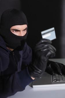 Hacker en pasamontañas gastando dinero en línea