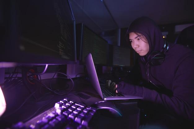 Hacker de seguridad cibernética asiático con capucha mientras trabaja en la programación en una habitación oscura, espacio de copia