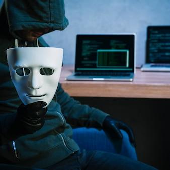 Hacker sujetando máscara