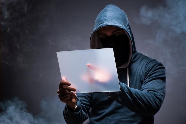 Hacker trabajando en tableta en la oscuridad