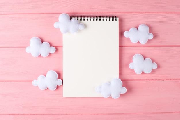 Haga las nubes blancas a mano con el cuaderno, copyspace en fondo de madera rosado. juguetes de fieltro hechos a mano.