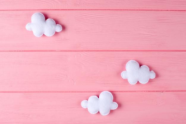 Haga las nubes blancas a mano con el marco, copyspace en fondo de madera rosado. juguetes de fieltro hechos a mano.