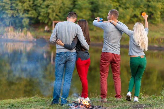 Haga un picnic con amigos en el lago cerca de la hoguera. amigos de la compañía que tienen fondo de naturaleza de picnic de caminata. excursionistas relajantes durante el tiempo de bebida. picnic de verano tiempo de diversión con amigos