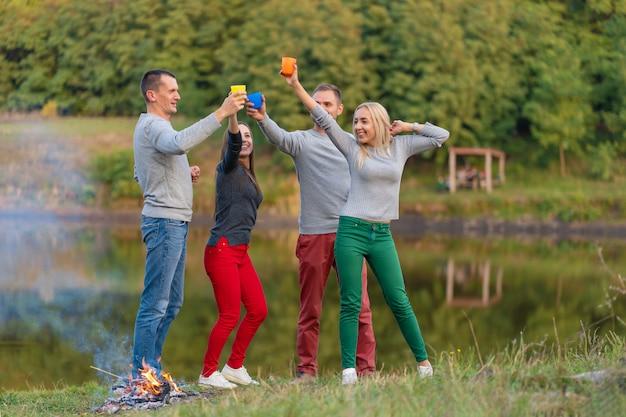 Haga un picnic con amigos en el lago cerca de la hoguera. amigos de la empresa haciendo un picnic