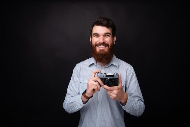 Hagamos algunas fotos. joven barbudo sosteniendo una cámara de fotos vintage sobre fondo negro.