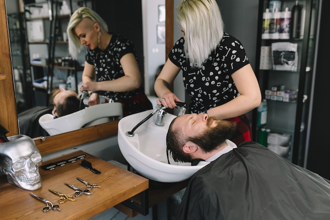 Hairstylist que lava el pelo del cliente en barbería.
