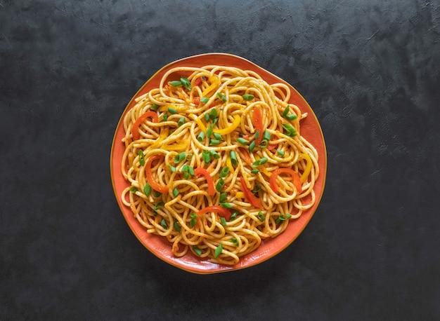 Hakka noodles es una receta popular indochina. schezwan fideos con verduras en un plato. vista superior.