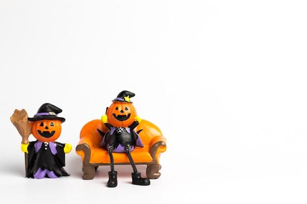 Halloween de calabaza de wizard sentado en un sofá naranja y calabaza de mago con una escoba