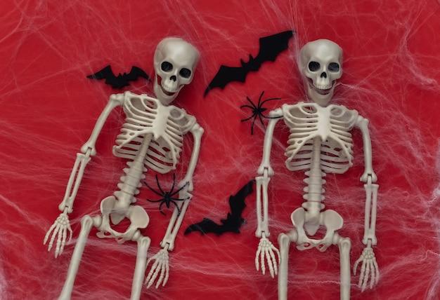 Halloween de miedo, decoración. dos esqueletos falsos, arañas con telaraña, murciélagos voladores en rojo