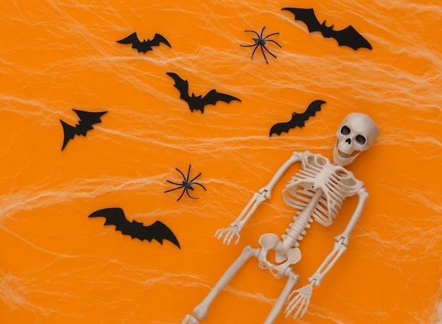 Halloween de miedo, decoración. esqueleto falso, arañas con telaraña, murciélagos voladores sobre un amarillo. truco o trato