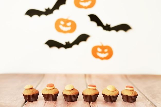 Halloween trata cupcakes en la mesa contra el fondo de calabazas y murciélagos