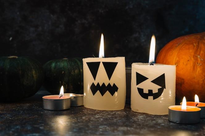 Halloween velas ardientes de pie rodeado de calabazas