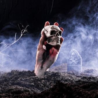 Halloween zombie mano sosteniendo el cráneo en el cementerio