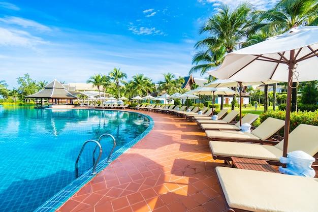 Hamacas y sombrillas puestas cercas de una piscina grande