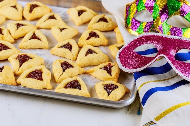 Hamantaschen galletas con mermelada en la bandeja para hornear con tallit y máscara.