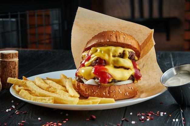 Hamburguesa apetitosa y jugosa con carne de res, queso cheddar derretido, salsa de tomate, cebolla y pepinos en vinagre en un plato blanco con papas fritas. de cerca