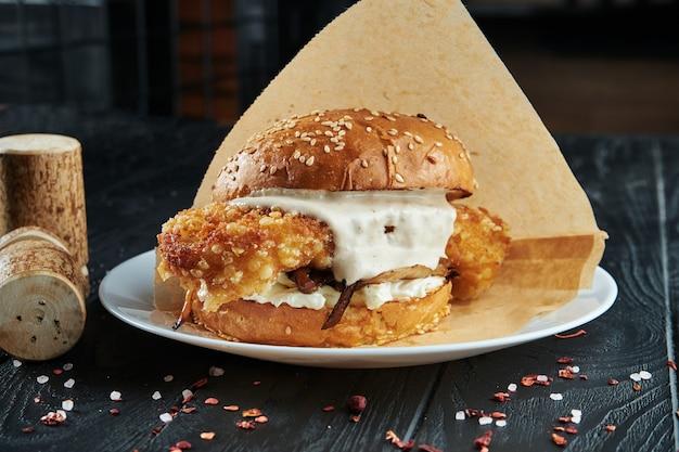 Hamburguesa apetitosa y jugosa con filete de pescado frito, salsa tártara blanca y queso en un plato blanco con papas fritas.