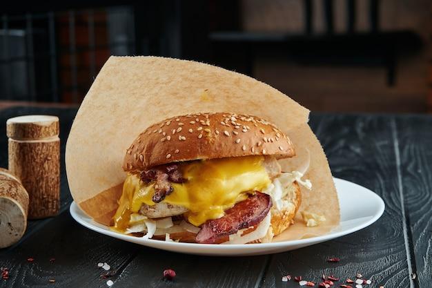 Hamburguesa apetitosa y jugosa con queso camembert, queso cheddar, tocino y cebolla en un plato blanco con papas fritas. de cerca