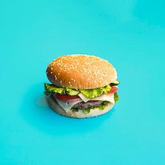 Hamburguesa apetitosa sobre fondo azul