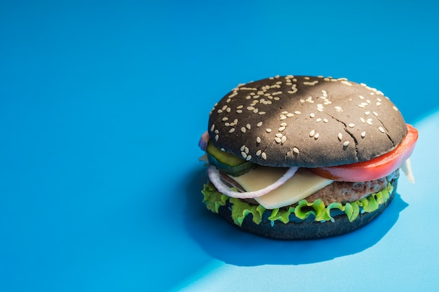 Hamburguesa con bollo negro sobre fondo azul.
