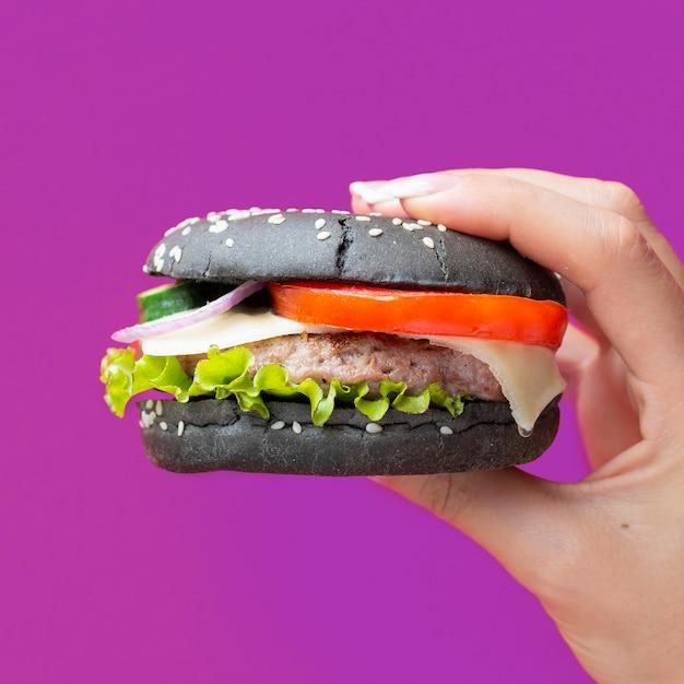 Hamburguesa con bollo negro sobre fondo morado