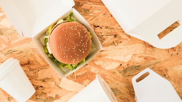 Hamburguesa en la caja con paquetes sobre fondo de madera.