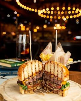Hamburguesa de carne en bollo de pan cortado en dos trozos.