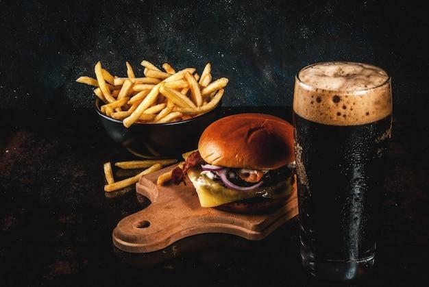 Hamburguesa de carne fresca y queso con papas fritas y un vaso de cerveza de jengibre oscuro, en azul oscuro,