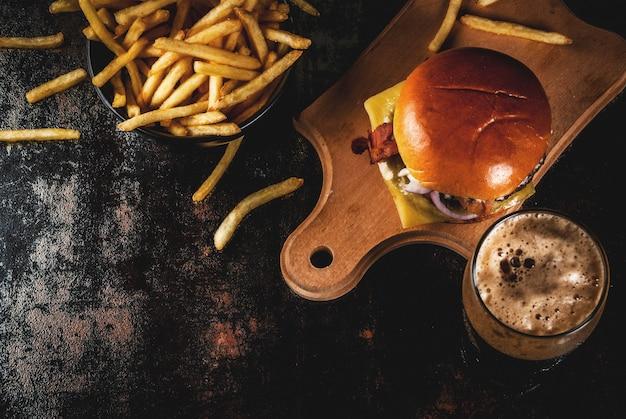 Hamburguesa de carne fresca y queso con papas fritas y un vaso de cerveza de jengibre oscuro