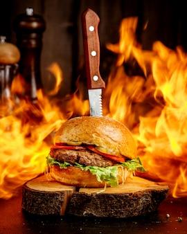 Hamburguesa de carne de fuego en un cáñamo de madera