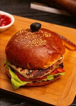 Hamburguesa de carne de pollo con rodajas de tomate y lechuga servida con salsa de tomate y mayonesa sobre tabla de madera