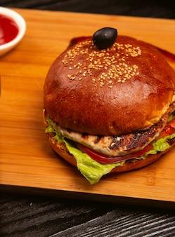 Hamburguesa de carne de pollo con tomate y lechuga en el interior servida con aceituna negra y salsa de tomate en una bandeja de madera.
