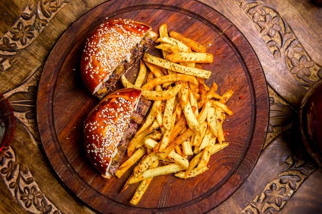 Hamburguesa de carne sobre tabla de madera papas fritas vista superior