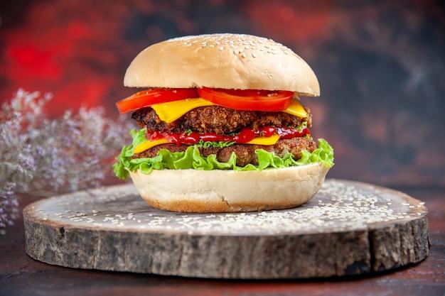 Hamburguesa de carne vista frontal con ensalada de queso y tomates en el fondo oscuro
