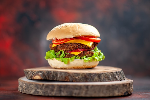 Hamburguesa de carne vista frontal con ensalada de queso y tomates sobre fondo oscuro