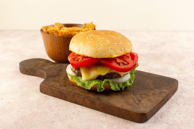 Una hamburguesa de carne de vista frontal con verduras, queso, ensalada verde y alitas de pollo en la mesa de madera