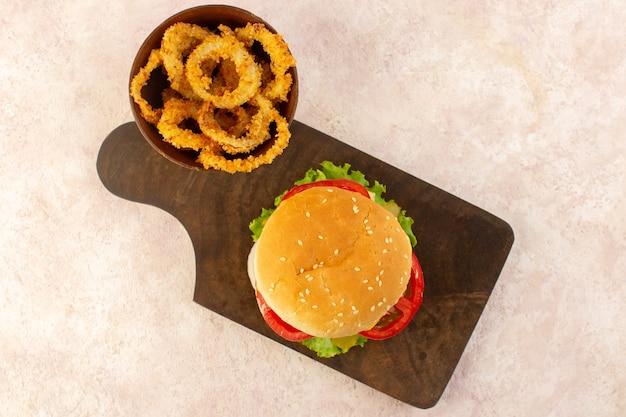 Una hamburguesa de carne de vista superior con verduras, queso, ensalada verde y alitas de pollo.
