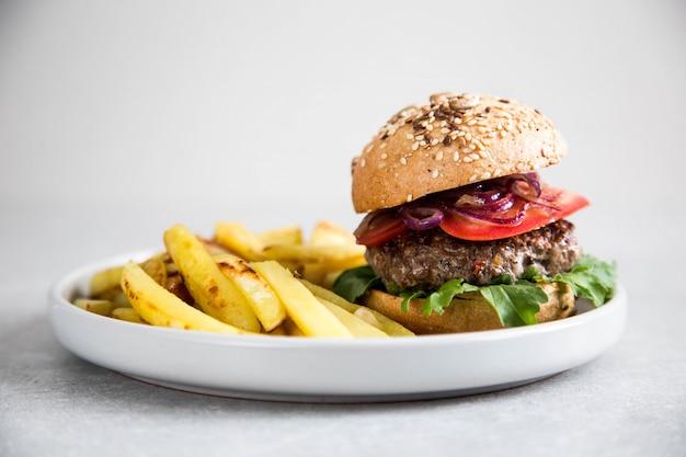 Hamburguesa casera artesana de carne y papas fritas.