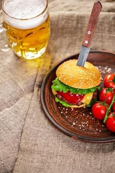 Hamburguesa casera de carne y verduras frescas en plato de arcilla con vaso de cerveza en la mesa de madera rústica.