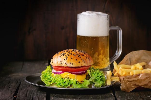 Hamburguesa casera con cerveza y papas.