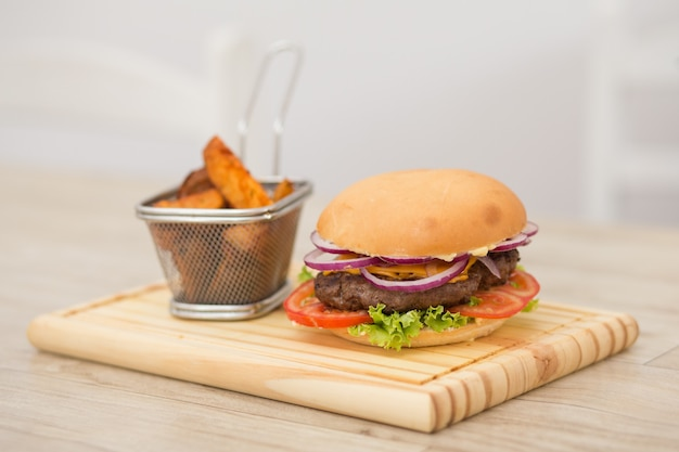 Hamburguesa casera fresca en una pequeña tabla de cortar con patatas asadas, servida con salsa de tomate y sal marina sobre una mesa de madera con fondo de madera gris.